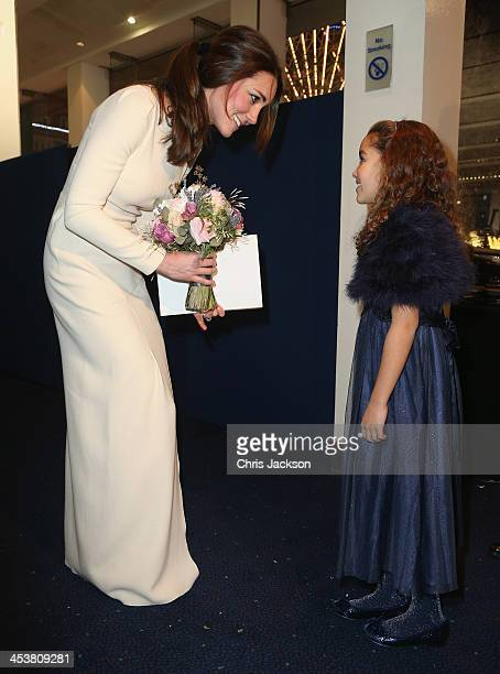 Catherine, Duchess of Cambridge is presented with a bouquet of flowers by a young girl as she attends the Royal film performance of 'Mandela: Long...