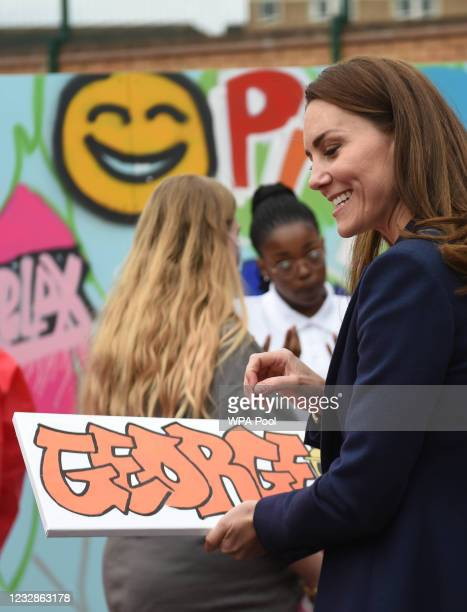 Catherine, Duchess of Cambridge is presented with a gift for Prince George during a visit to The Way Youth Zone on May 13, 2021 in Wolverhampton,...