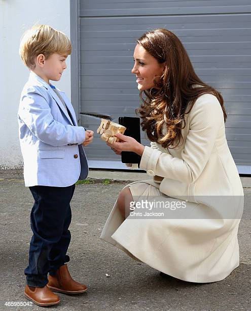 Catherine Duchess of Cambridge is presented with a train for Prince George by actor Oliver Barker during an official visit to the set of Downton...
