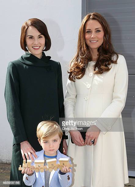 Catherine Duchess of Cambridge is presented with a train for Prince George by actor Oliver Barker and actress Michelle Dockery during an official...