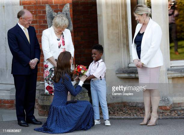 Catherine Duchess of Cambridge is presented with flowers by Lawson Bischoff after visiting the DDay exhibition at Bletchley Park on May 14 2019 in...