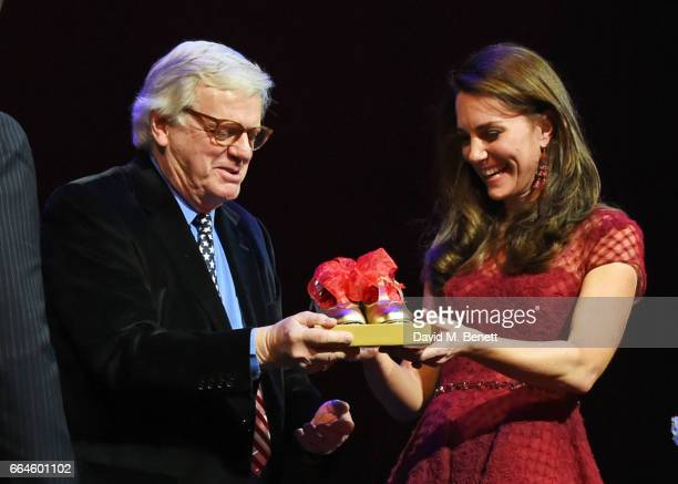 Catherine Duchess of Cambridge is presented with tap shoes by producer Michael Grade during the Opening Night Royal Gala performance of 42nd Street...