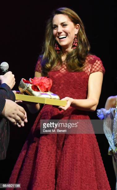 Catherine Duchess of Cambridge is presented with tap shoes during the Opening Night Royal Gala performance of '42nd Street' in aid of the East Anglia...