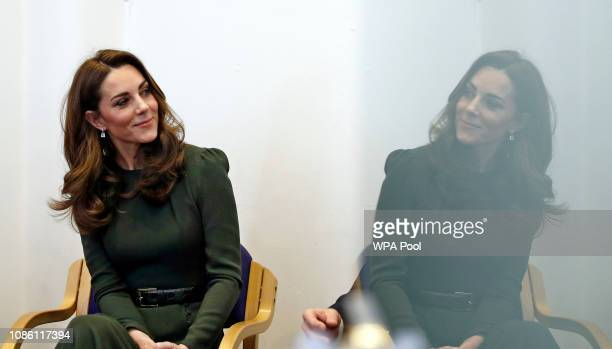 Catherine Duchess of Cambridge is reflected in a glass door as she looks towards Family Action CEO David Holmes during a visit to a new national...