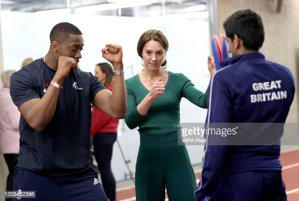 Catherine, Duchess of Cambridge is shown Taekwondo moves by Great Britain's Lutalo Muhammad during a SportsAid Stars event at the London Stadium in...