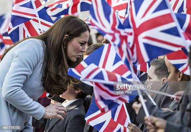 Catherine Duchess of Cambridge is surrounded by local school children waving Union Jack flags as she arrives to open the new Kensington Leisure...