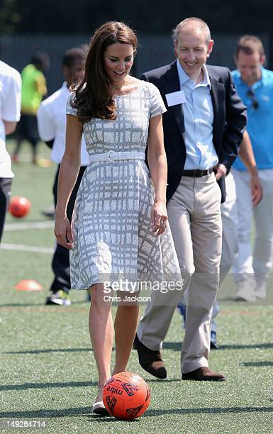 Catherine, Duchess of Cambridge kicks a football on the football pitch as she visits Bacon's College on July 26, 2012 in London, England. Prince...