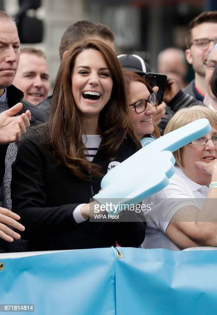 Catherine Duchess of Cambridge laughs as she wears a big foam hand passed to her to put on by Prince Harry as they cheer on runners at a 'Heads...