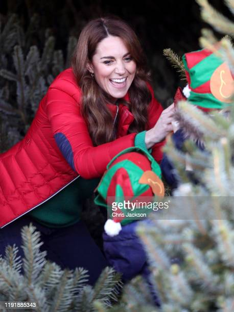 Catherine Duchess of Cambridge laughs with a young child as she helps pick Christmas trees for preschool during a visit to the charity Family Action...