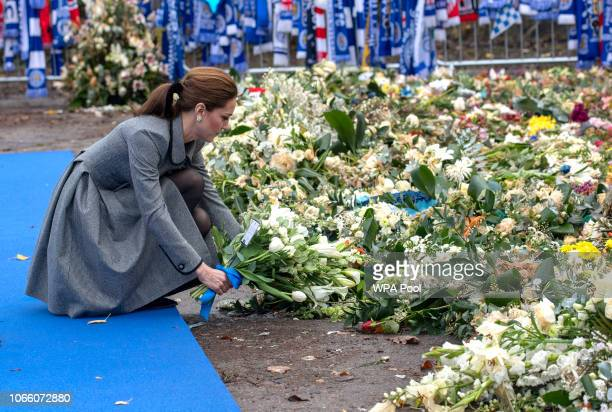Catherine Duchess of Cambridge lays flowers during a visit to Leicester City Football Club where they paid their respects to the victims of October's...
