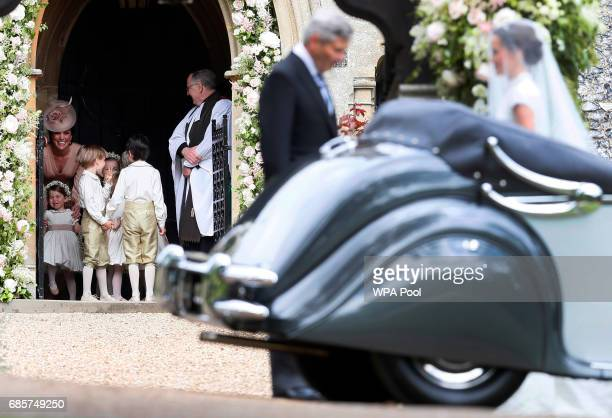 Catherine Duchess of Cambridge left stands with her daughter Princess Charlotte bottom left as they arrive for the wedding of Pippa Middleton right...