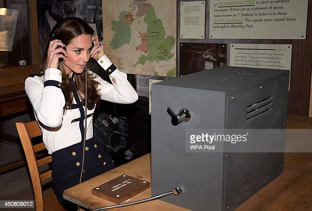 Catherine Duchess Of Cambridge listens to a morse code message using a replica radio during a tour the of the restored WWII Codebreaking Huts at...