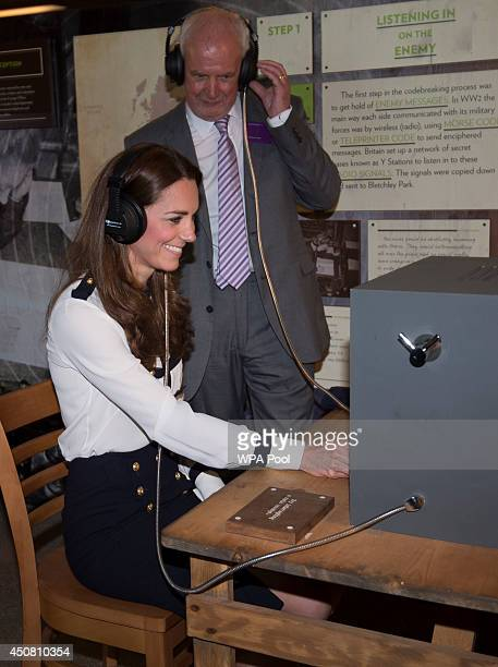 Catherine Duchess Of Cambridge listens to a morse code message using a replica radio with event manager Steve Lumby during a tour the of the restored...