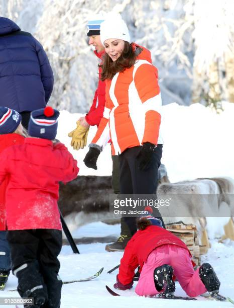 Catherine Duchess of Cambridge looks back as a small girl falls over as she attends an event organised by the Norwegian Ski Federation with Prince...