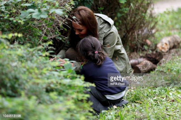 Catherine Duchess of Cambridge looks for bugs with a pupil from St Augustines School during a visit to Sayers Croft Forest School and Wildlife Garden...