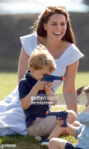Catherine Duchess of Cambridge looks on as Prince George of Cambridge plays with a toy gun whilst attending the Maserati Royal Charity Polo Trophy at...