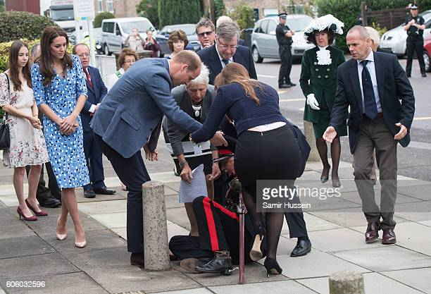 Catherine Duchess of Cambridge looks on as Prince William Duke of Cambridge helps up Jonathan DouglasHughes vice Vice LordLieutenant of Essex after...