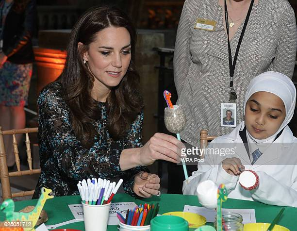 Catherine Duchess of Cambridge makes a dinosaur egg whilst attending a children's tea party with pupils from Oakington Manor Primary School in...