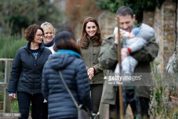 Catherine, Duchess of Cambridge meets a young baby as she visits Islington Community Garden on January 15, 2019 in London, England.