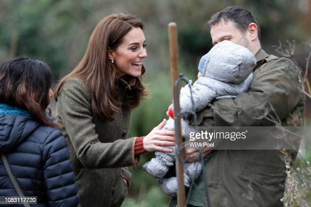 Catherine Duchess of Cambridge meets a young baby as she visits Islington Community Garden on January 15 2019 in London England