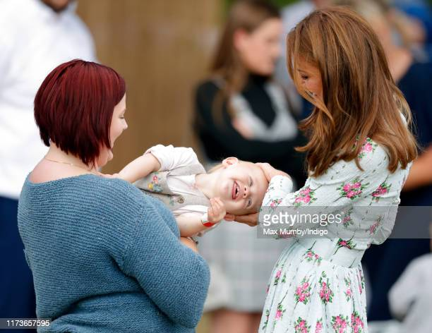 """Catherine, Duchess of Cambridge meets a young toddler as she attends the """"Back to Nature"""" festival at RHS Garden Wisley on September 10, 2019 in..."""