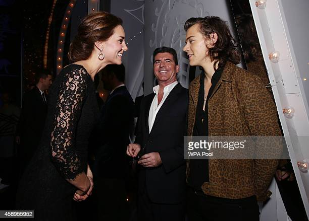 Catherine Duchess of Cambridge meets Harry Styles of One Direction as Simon Cowell looks on at the end of The Royal Variety Performance at the London...