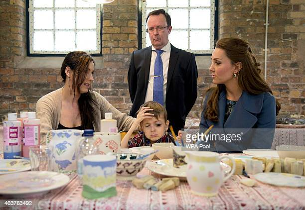 Catherine Duchess of Cambridge meets Sarah O'Sullivan and her disabled 4yearold son Daniel as they decorate crockery during a visit to the 'Emma...