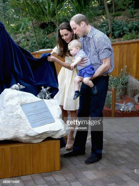 Catherine Duchess of Cambridge picks up a toy bilby Prince George of Cambridge threw on the ground as Prince William Duke of Cambridge holds Prince...