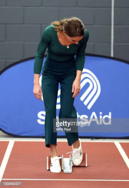 Catherine, Duchess of Cambridge places her feet in starting blocks during a SportsAid Stars event at the London Stadium in Stratford on February 26,...