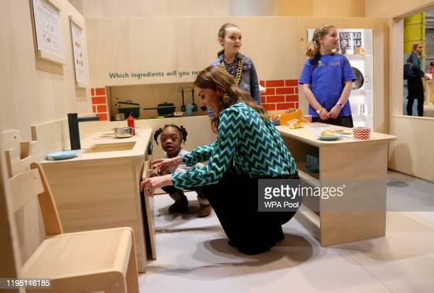 Catherine Duchess of Cambridge plays with a child as she visits MiniBrum an interactive childsized world at Thinktank at Birmingham Science Museum on...