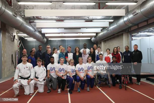 Catherine, Duchess of Cambridge poses for a photograph with young athletes and staff during a SportsAid Stars event at the London Stadium in...