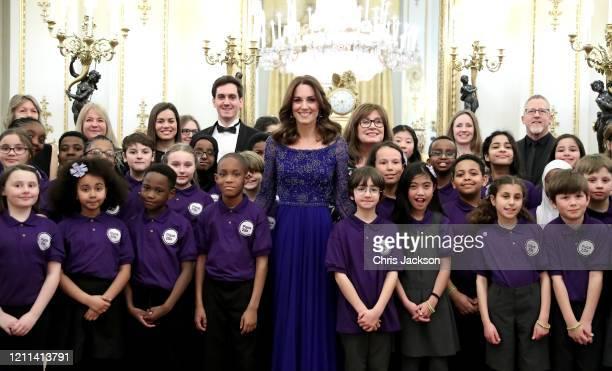 Catherine Duchess of Cambridge poses with two school choirs supporters and guests as she hosts a Gala Dinner in celebration of the 25th anniversary...