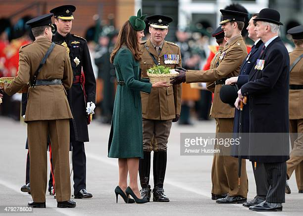 Catherine Duchess of Cambridge presents shamrocks during the St Patrick's Day Parade at Mons Barracks on March 17 2014 in Aldershot England