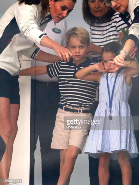 Catherine, Duchess of Cambridge, Prince George of Cambridge and Princess Charlotte of Cambridge look through a window at the prize giving after the...