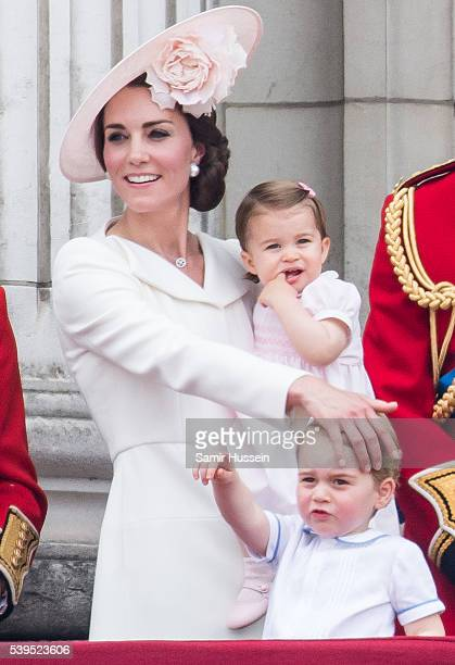 Catherine, Duchess of Cambridge, Princess Charlotte, Prince George stand on the balcony during the Trooping the Colour, this year marking the Queen's...
