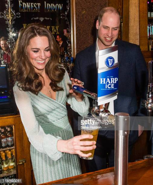 Catherine, Duchess of Cambridge pulls a pint of beer as Prince William, Duke of Cambridge looks on during a visit to Empire Music Hall Belfast on...