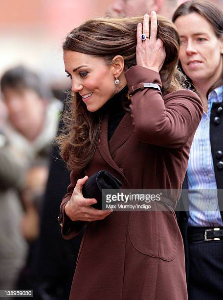 Catherine, Duchess of Cambridge pulls her hair back during as walkabout as she visits Alder Hey Children's Hospital on February 14, 2012 in...