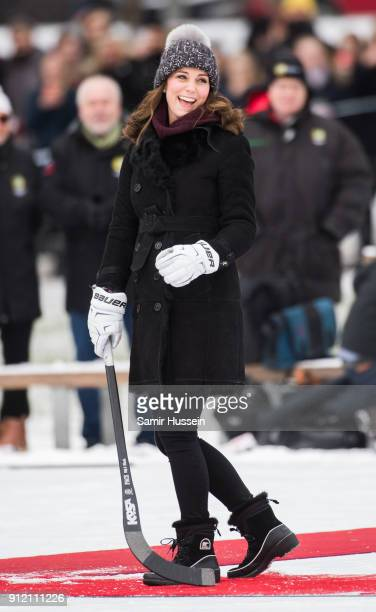 Catherine Duchess of Cambridge reacts after hitting the ball as she attends a Bandy hockey match with Prince William Duke of Cambridge where they...