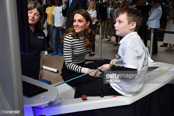 Catherine Duchess of Cambridge reacts as she uses a sailing dinghy simulator during the launch the King's Cup Regatta at Cutty Sark Greenwich on May...