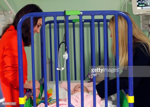 Catherine Duchess of Cambridge reacts to 6 month old patient Sienna McGuire as she visits Great Ormond Street Hospital to officially open the Mittal...