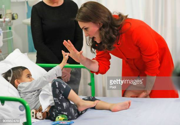 Catherine Duchess of Cambridge reacts to patient Rafael Chana as she visits Great Ormond Street Hospital to officially open the Mittal Children's...