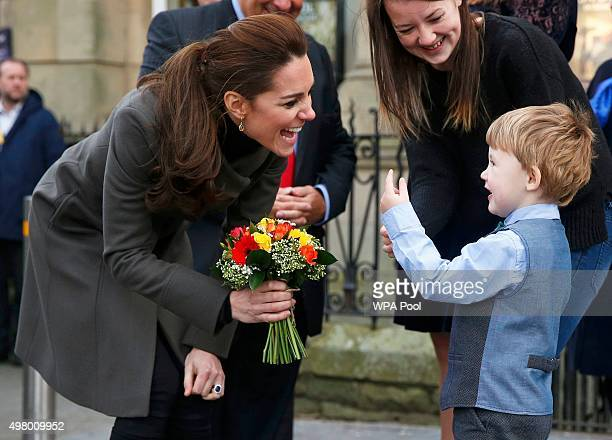 Catherine Duchess of Cambridge receives a bunch of flowers from Theo Hayward aged three as she leaves after visiting a GISDA centre during a visit to...