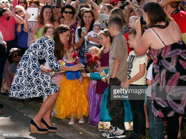 Catherine Duchess of Cambridge receives a flower from a girl as she meets locals as she tours the Blue Mountains suburb of Winmalee with her husband...