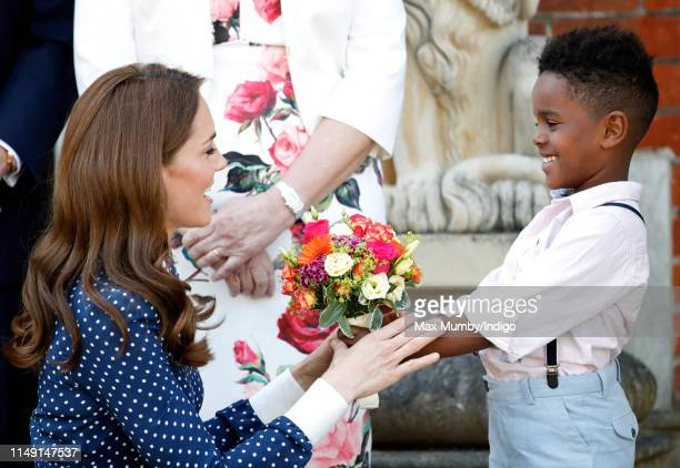 Catherine Duchess of Cambridge receives a posy of flowers as she visits the 'DDay Interception Intelligence Invasion' exhibition at Bletchley Park on...