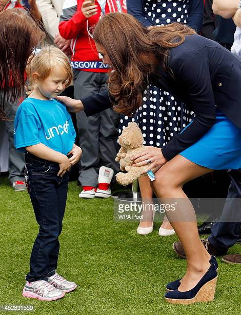 Catherine Duchess of Cambridge receives a teddy from Kacey Armstronge during a visit to the Commonwealth Games Village on July 29 2014 in Glasgow...