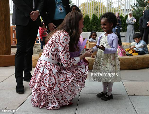 Catherine Duchess of Cambridge receives flowers from a young girl during their visit to the Immigrant Services Society of British Columbia New...