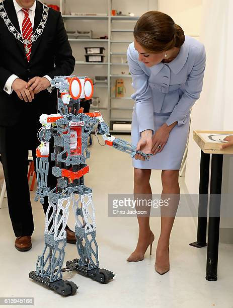 Catherine Duchess of Cambridge shakes hands with a robot during a class at Bouwkeet workshop project for teenagers on October 11 2016 in Rotterdam...