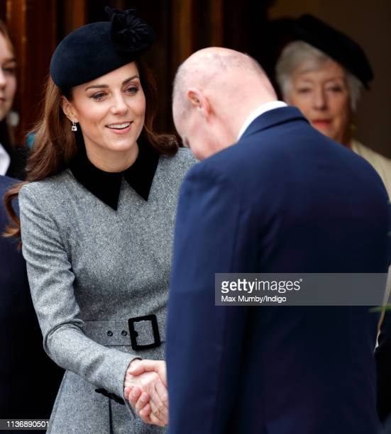 Catherine Duchess of Cambridge shakes hands with Lord Christopher Geidt as she accompanies Queen Elizabeth II on a visit to King's College London to...