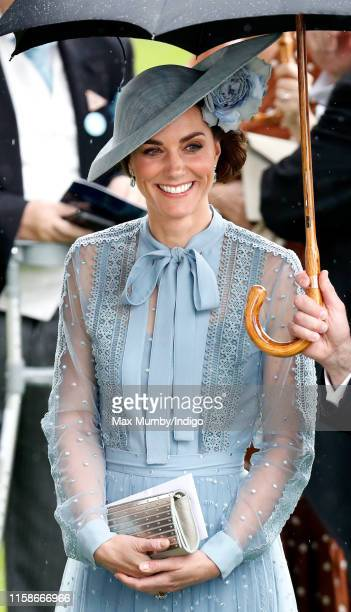 Catherine Duchess of Cambridge shelters under an umbrella as she attends day one of Royal Ascot at Ascot Racecourse on June 18 2019 in Ascot England