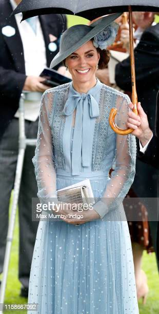 Catherine, Duchess of Cambridge shelters under an umbrella as she attends day one of Royal Ascot at Ascot Racecourse on June 18, 2019 in Ascot,...
